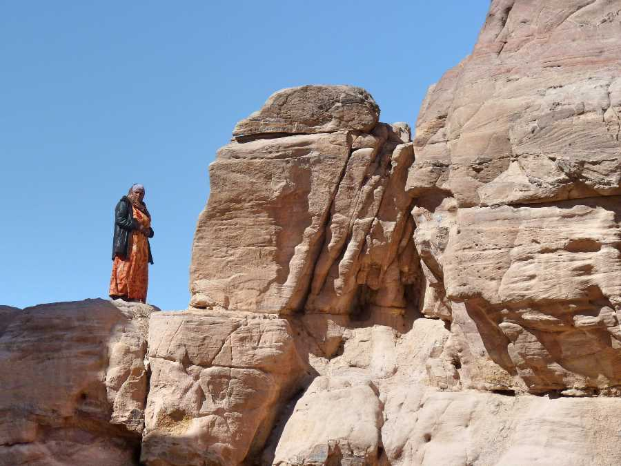 A woman stands on a rock